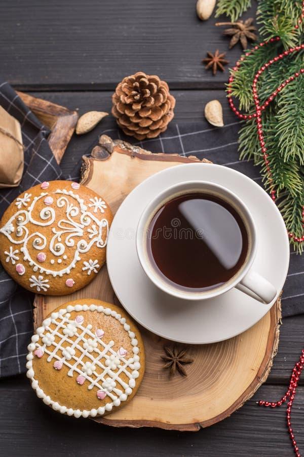 Kopp av svart kaffe med julpepparkakakakor på svart royaltyfri foto