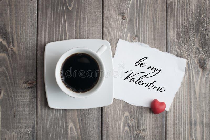 Kopp av svart kaffe och att älska valentin dagmeddelandet med röd hjärtaform royaltyfria foton
