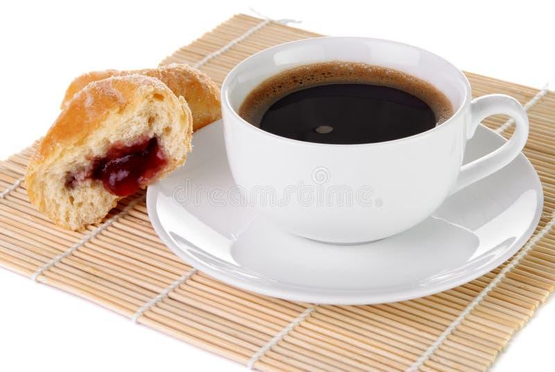Kopp av svart kaffe och en munk royaltyfri bild