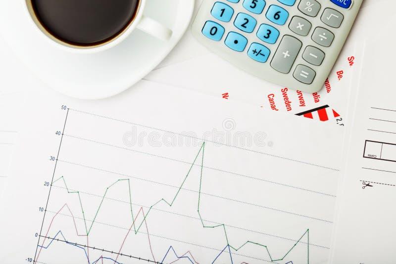 Kopp av svart kaffe och räknemaskinen över någon finansiell documantation - nära övre studioskott arkivbilder