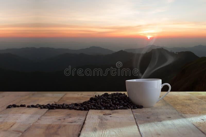 Kopp av svart kaffe och solnedgången arkivfoton