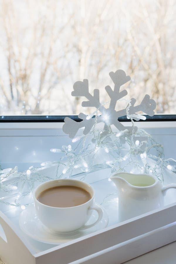 Kopp av svart kaffe på vinterfönsterbräda Xmas-ferietid royaltyfria foton