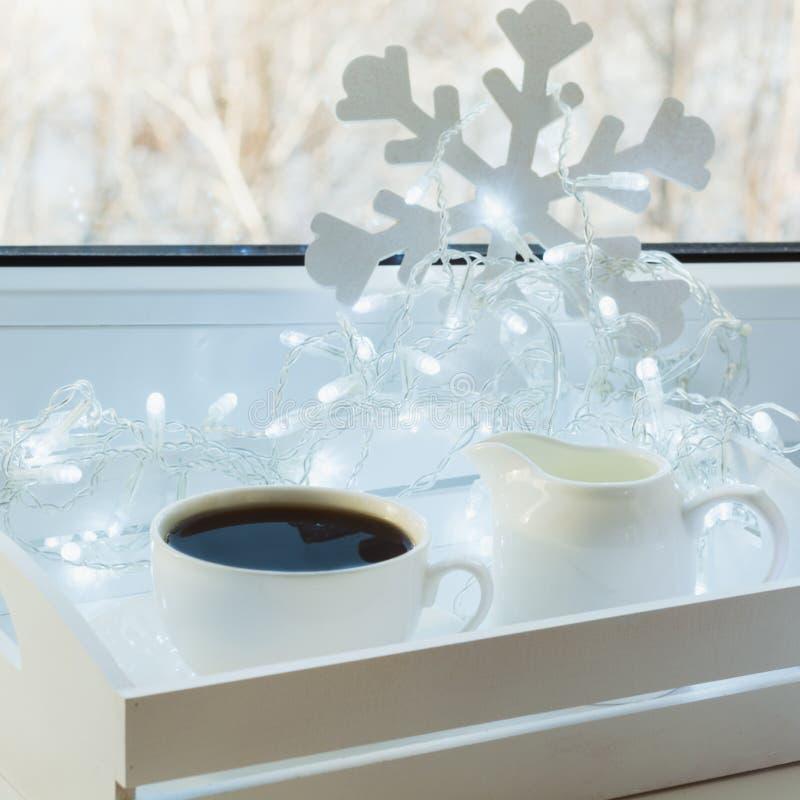Kopp av svart kaffe på vinterfönsterbräda Xmas-ferietid arkivbilder