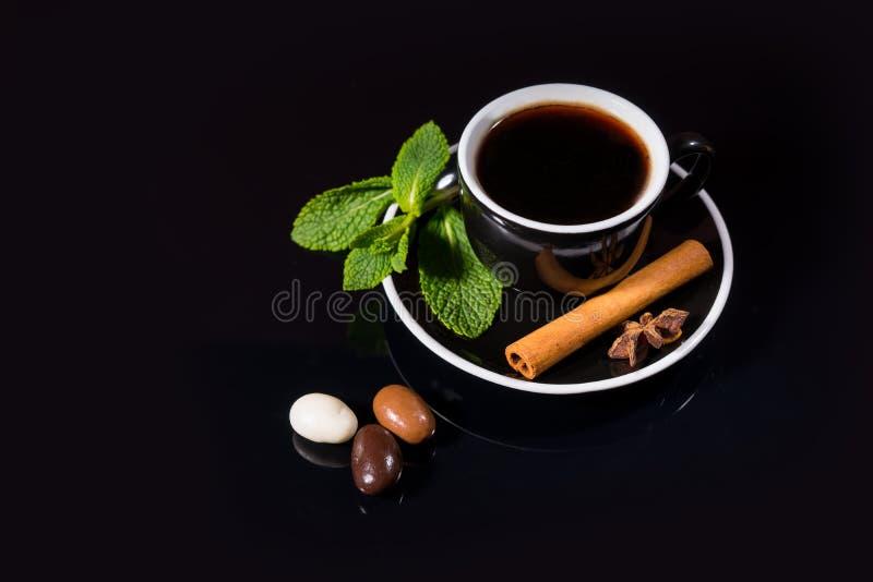 Kopp av svart te med godisen och smaktillsatser royaltyfria foton