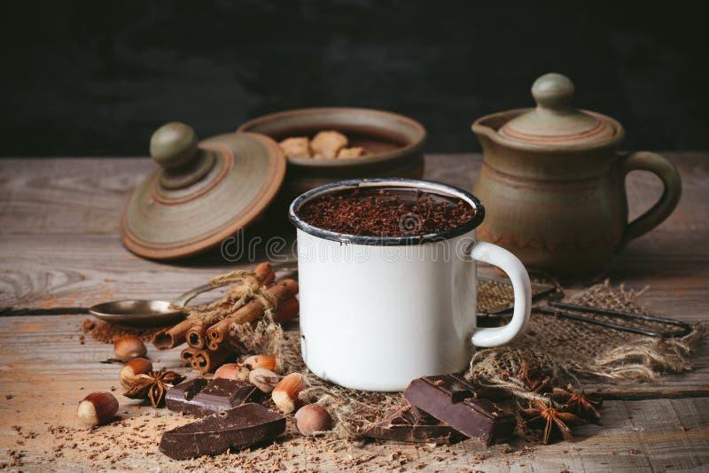 Kopp av varm choklad, kanelbruna pinnar, muttrar och choklad royaltyfri fotografi
