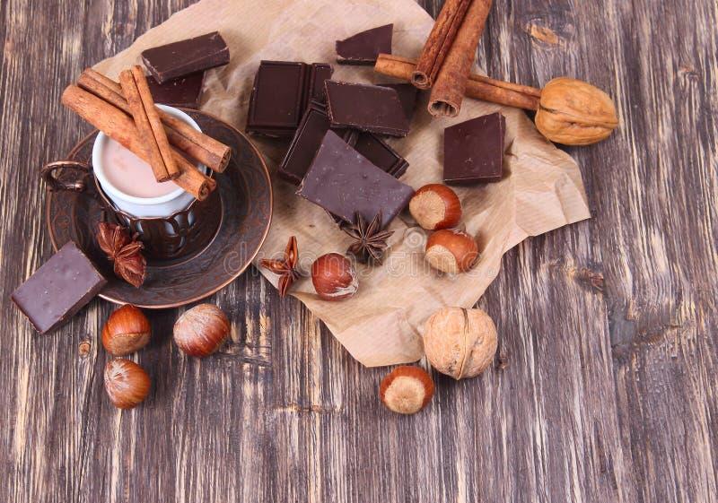 Kopp av varm choklad, kanelbruna pinnar, muttrar och choklad på trätabellen på brun bakgrund royaltyfri bild