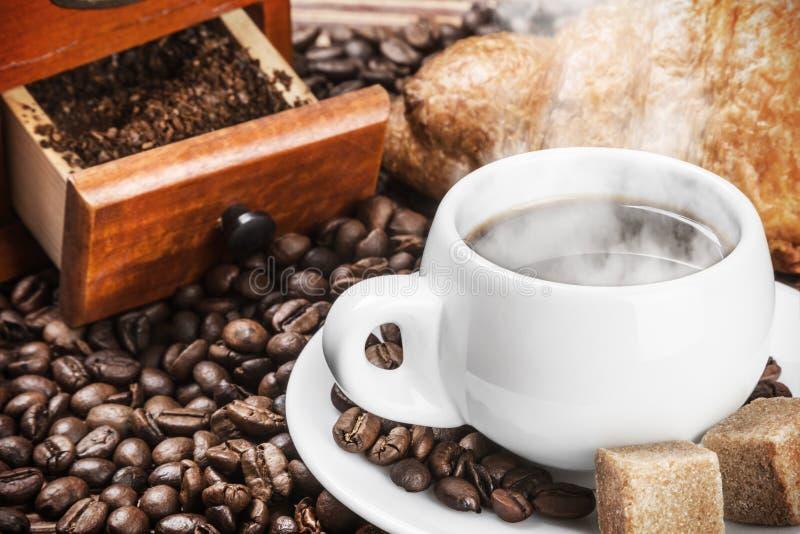 Kopp av varma kaffe och kaffebönor royaltyfri bild