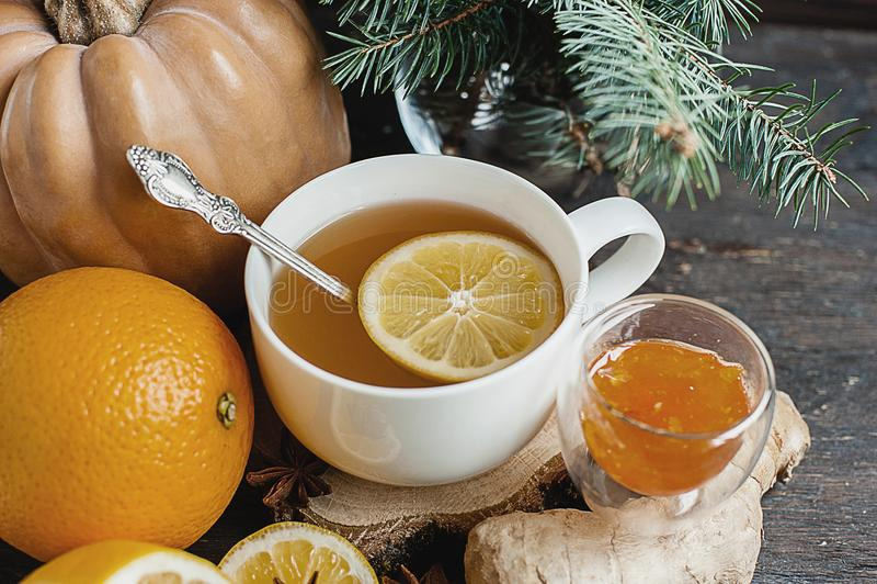 Kopp av varmt citronte med orange pumpa och ljust rödbrun driftstopp på en träbakgrund Sund drinkförkylning Vinterdrink royaltyfri bild