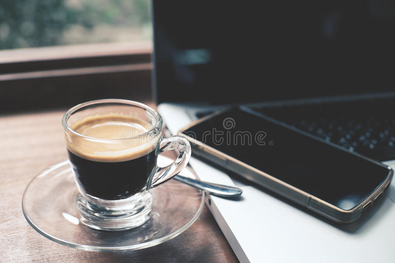 Kopp av varmt espressokaffe med bärbara datorn och smartphonen arkivbild
