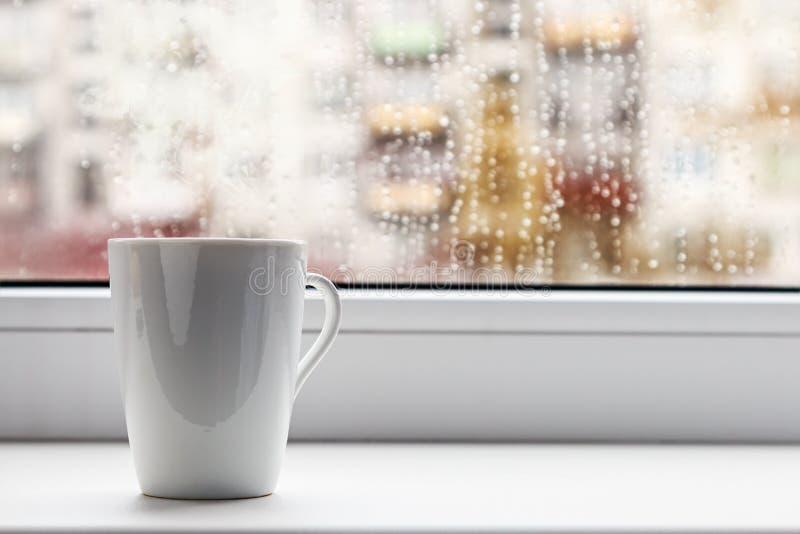 Kopp av varmt kaffe på fönstret fotografering för bildbyråer