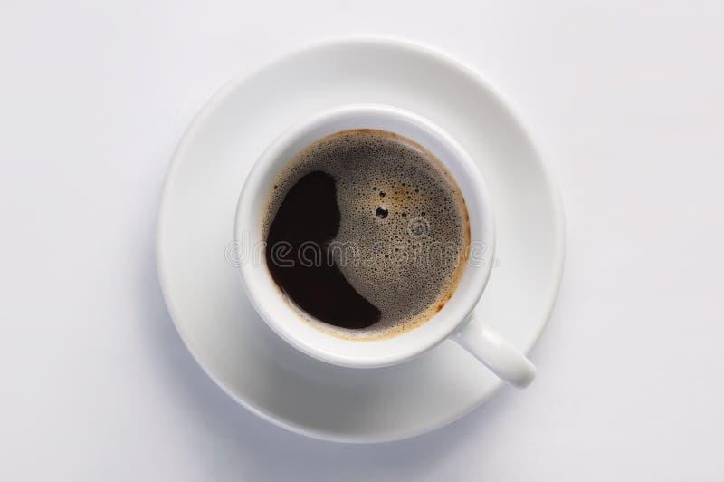 Kopp av varmt nytt svart kaffe med skum mot vit bakgrund som beskådas från överkant royaltyfri fotografi