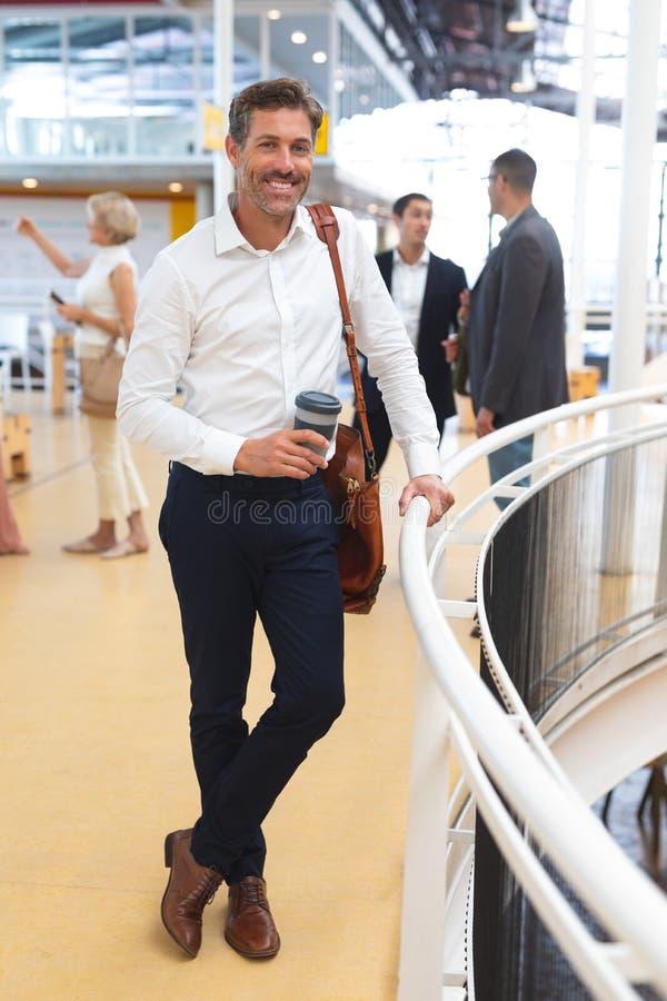 Kopp för kaffe för affärsmaninnehav disponibel och se kameran nära räcket i ett modernt kontor royaltyfria bilder