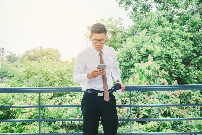 Kopp för kaffe för affärsmanUsing Mobile Phone hand utomhus- hållande royaltyfri foto