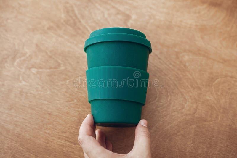 Kopp för kaffe för handinnehaveco på träbakgrund Kaffekopp från bambufiber, nollförlorat begrepp Enkel bruksplast- för förbud tak royaltyfria bilder