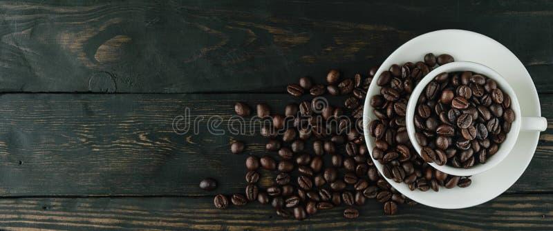 Kopp för kaffebönor på svart wood bästa sikt arkivbilder
