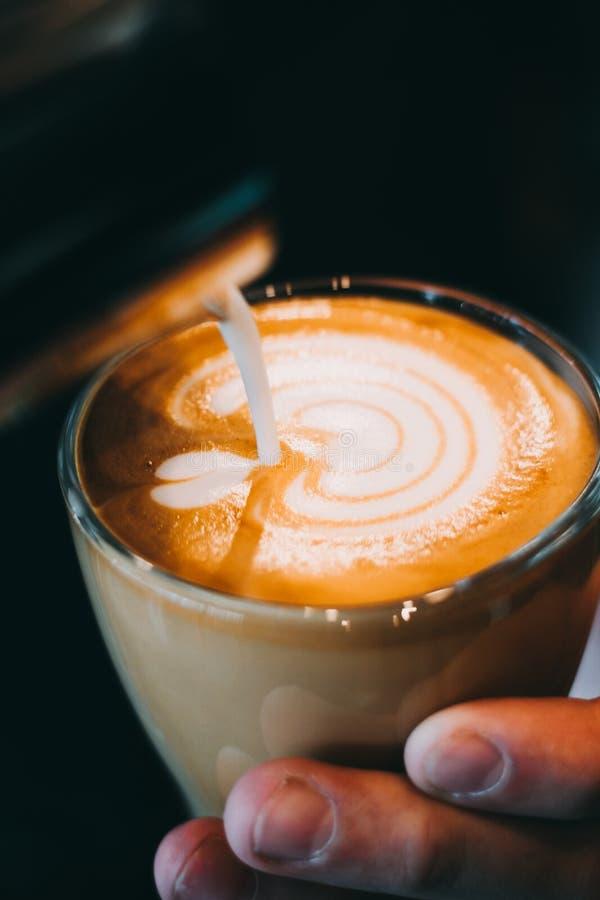 Kopp för Lattekonstkaffe - tappningeffekt arkivbild