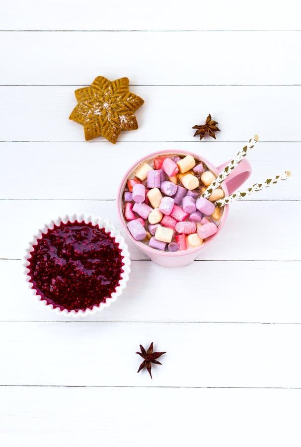 Kopp för rosa färger för julkakaomarshmallow och för tabellhallon för ingefära ljusbrunt vitt trädriftstopp arkivbild