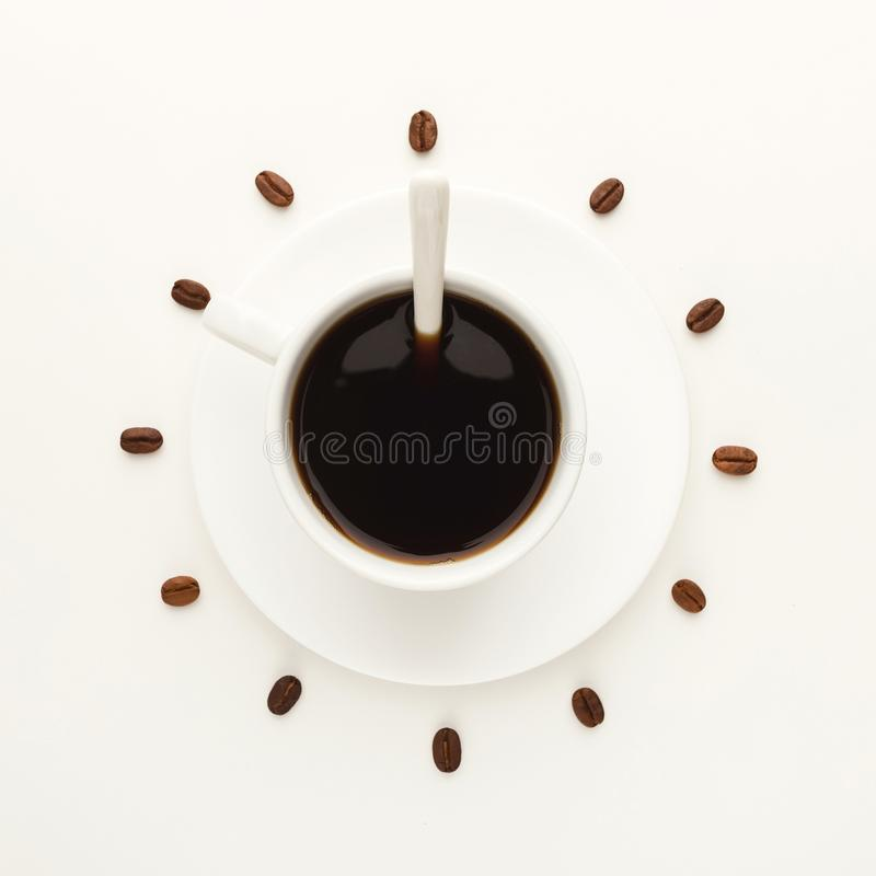 Kopp för svart kaffe och grillade bönor som bildar klockavisartavlan som isoleras på vit arkivbild