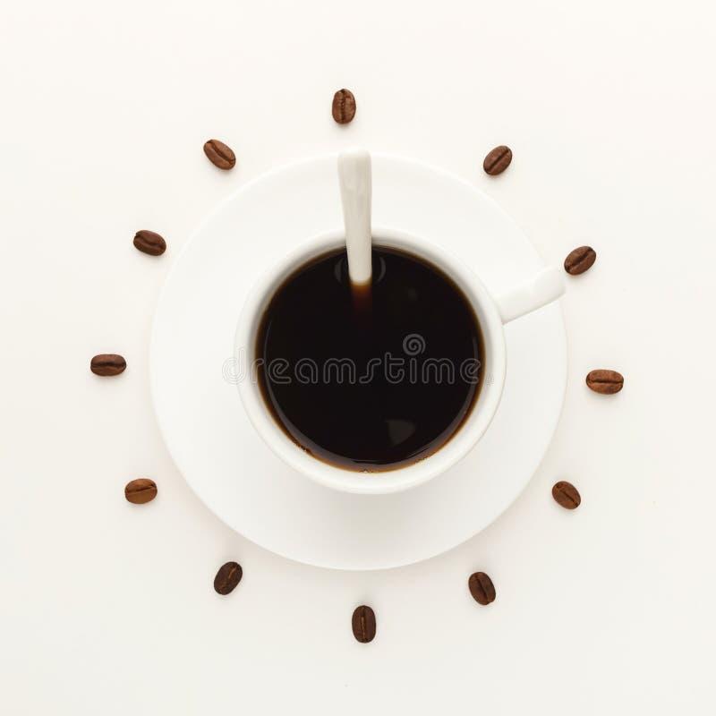 Kopp för svart kaffe och grillade bönor som bildar klockavisartavlan på vit arkivfoton