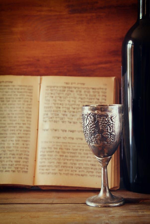 Kopp för tappningshabbathsilver av vin framme av torahbönboken royaltyfri bild