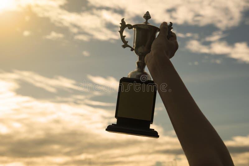 Kopp för trofé för vinnare för konturhand hållande i en mästerskap royaltyfri foto