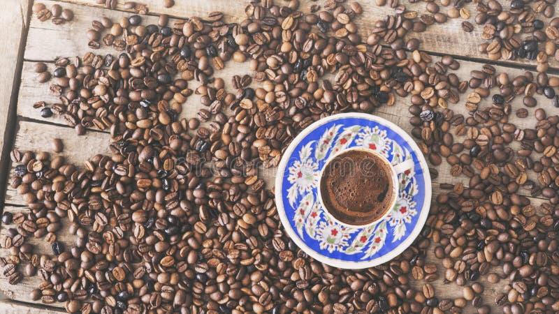 Kopp för turkiskt kaffe och kaffebönor på träbakgrund royaltyfri foto