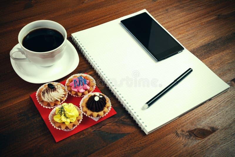 Kopp för vitt kaffe med anteckningsboken, fyra muffin, smartphone arkivfoton