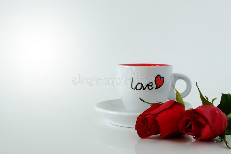 Kopp för vitt kaffe med ordet FÖRÄLSKELSE och par av rosor på vit bakgrund royaltyfri fotografi