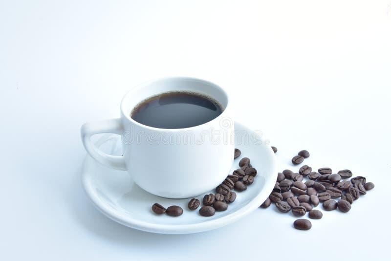 kopp för vitt kaffe och kaffeböna på vit bakgrund arkivfoto