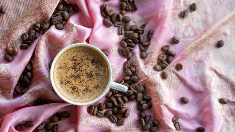 Kopp f?r vitt kaffe och kaffeb?nor runt om den med traditionell tygbakgrund royaltyfri illustrationer