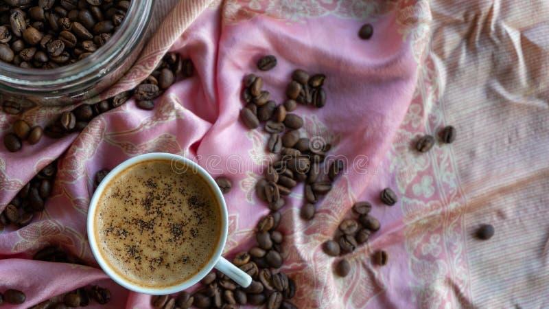 Kopp f?r vitt kaffe och kaffeb?nor runt om den med traditionell tygbakgrund stock illustrationer