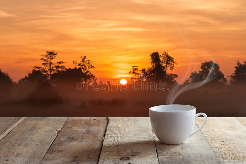 Kopp kaffe över den wood tabellen och solnedgång arkivfoto
