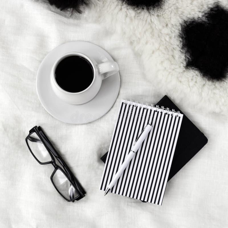 Kopp kaffe, anteckningsböcker, penna och glasögon på sängen arkivbilder
