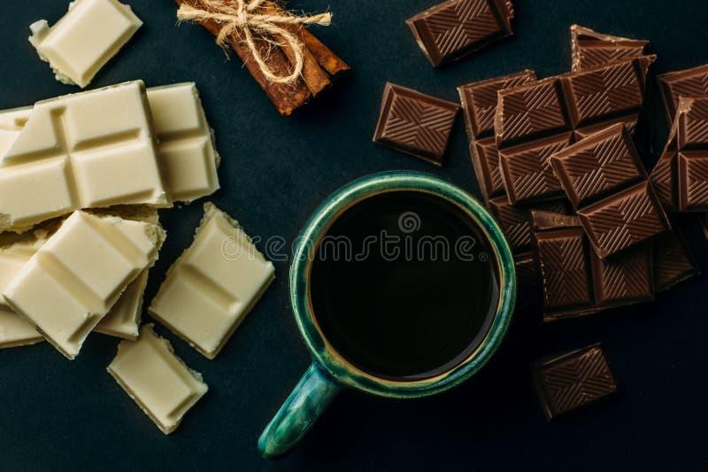 Kopp kaffe, brutna vit- och svartchokladstänger och bunt av kanel på den svarta tabellen, bästa sikt Smaklig energikalorimat royaltyfri bild