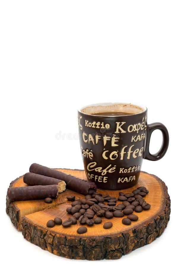 Kopp kaffe, chokladrullar och kaffebönor på stubben arkivfoto
