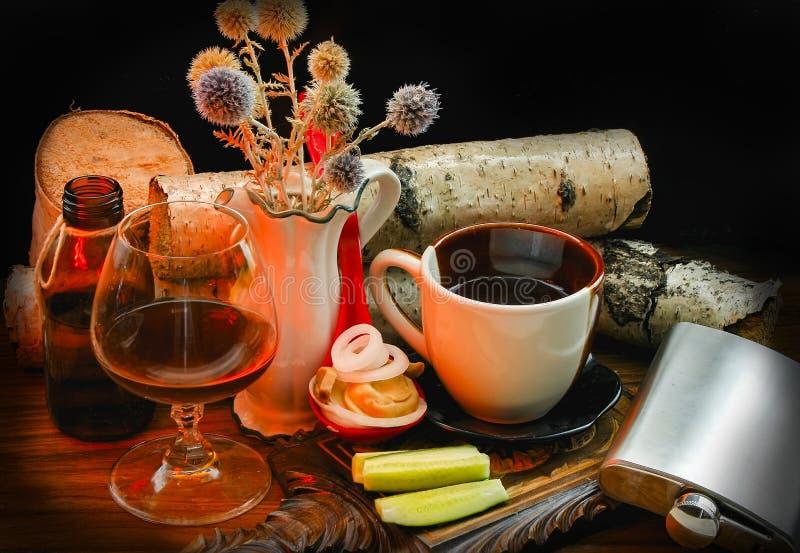Kopp kaffe, ett exponeringsglas av konjak på en svart bakgrund av björkjournaler och vildblommor royaltyfria bilder