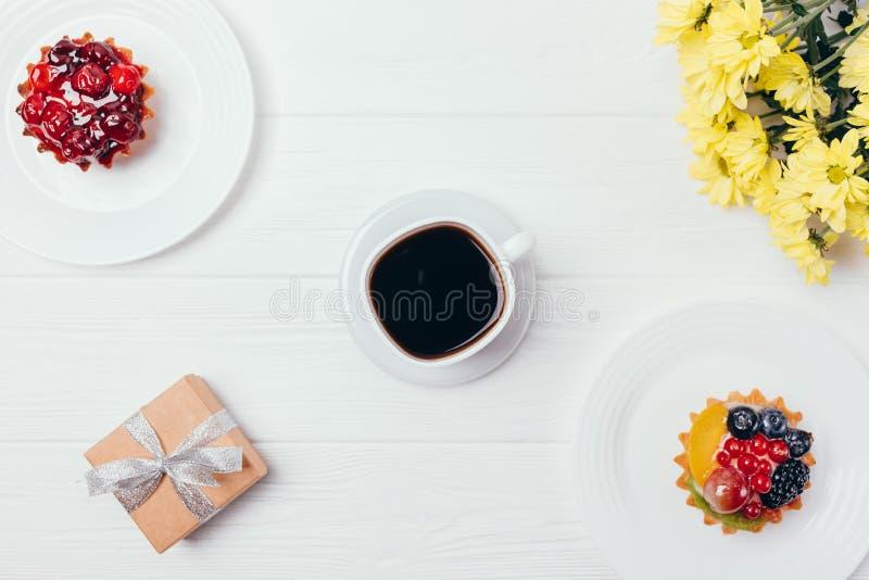 Kopp kaffe för bästa sikt på den vita trätabellen royaltyfri foto