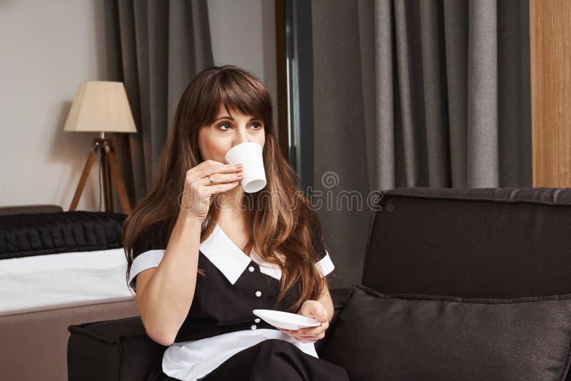 Kopp kaffe för husa av året Stående av den drömlika propra hembiträdet i likformig som läppjar te, medan se åt sidan och sitta arkivbild