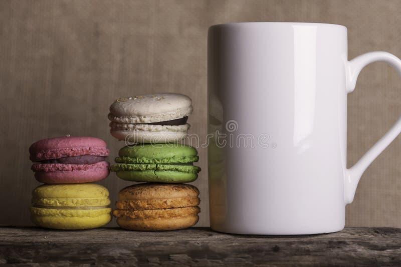 Kopp kaffe för sidosikt och kakamakronträbakgrund royaltyfri bild