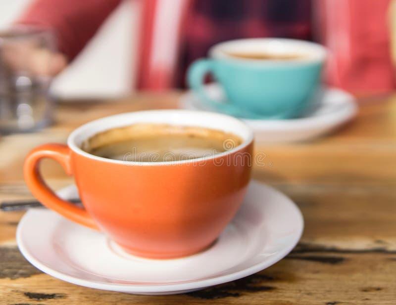 Kopp kaffe i en ljus orange kopp bredvid en kopp kaffe i ljus - blåttkopp royaltyfri bild