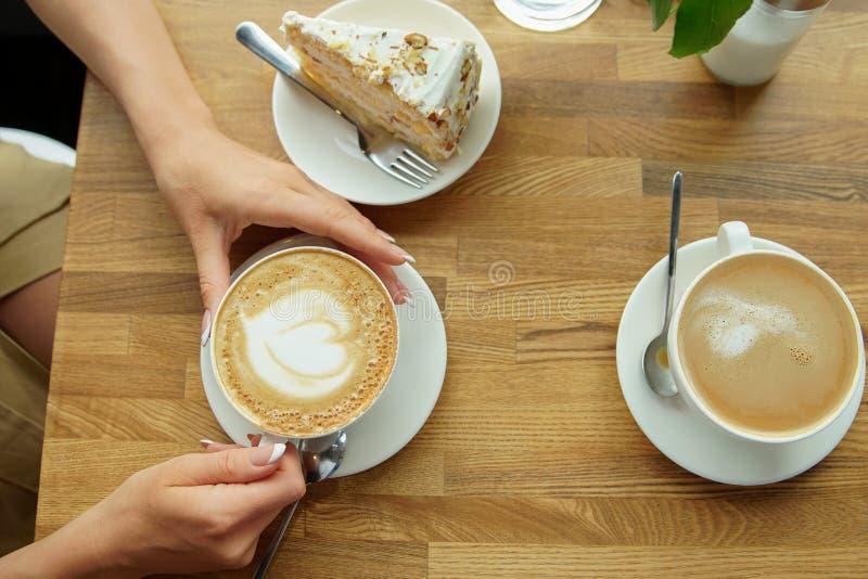Kopp kaffe i händer för ett kafé och för flicka` ett s Närbild av händer för kvinna` som s sitter med koppen kaffe i kaffehus royaltyfri fotografi