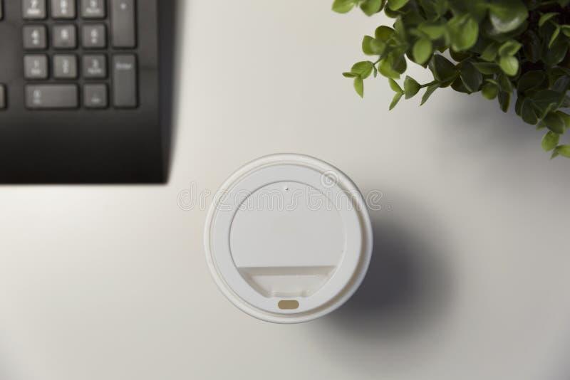 Kopp kaffe i regeringsställning bredvid datoren Arbetande sent begrepp royaltyfri fotografi