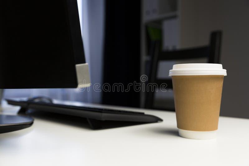 Kopp kaffe i regeringsställning bredvid datoren Arbetande sent begrepp arkivfoto