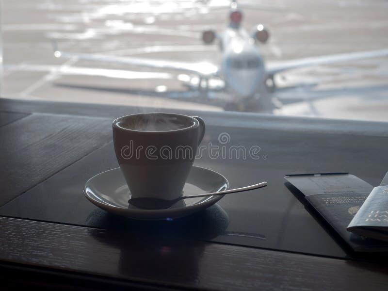 Kopp kaffe i vardagsrum för affär för flygplats` s med flygplan arkivfoto