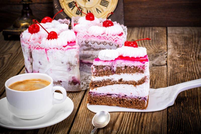 Kopp kaffe, kaka med kräm och körsbär royaltyfri bild