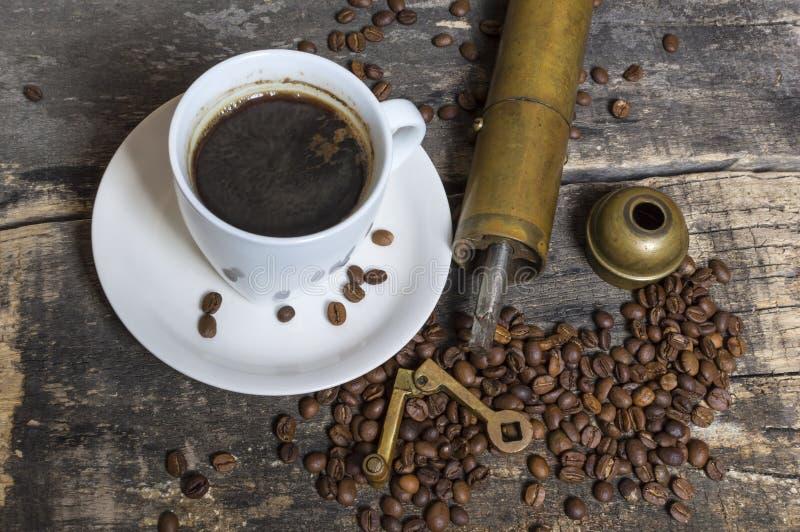 Kopp kaffe med bönor och kaffekvarnen på trätabellen arkivfoton