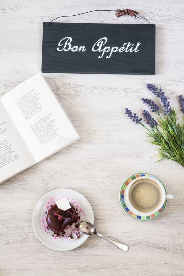 Kopp kaffe med efterrätten och boken på tabellen royaltyfria foton