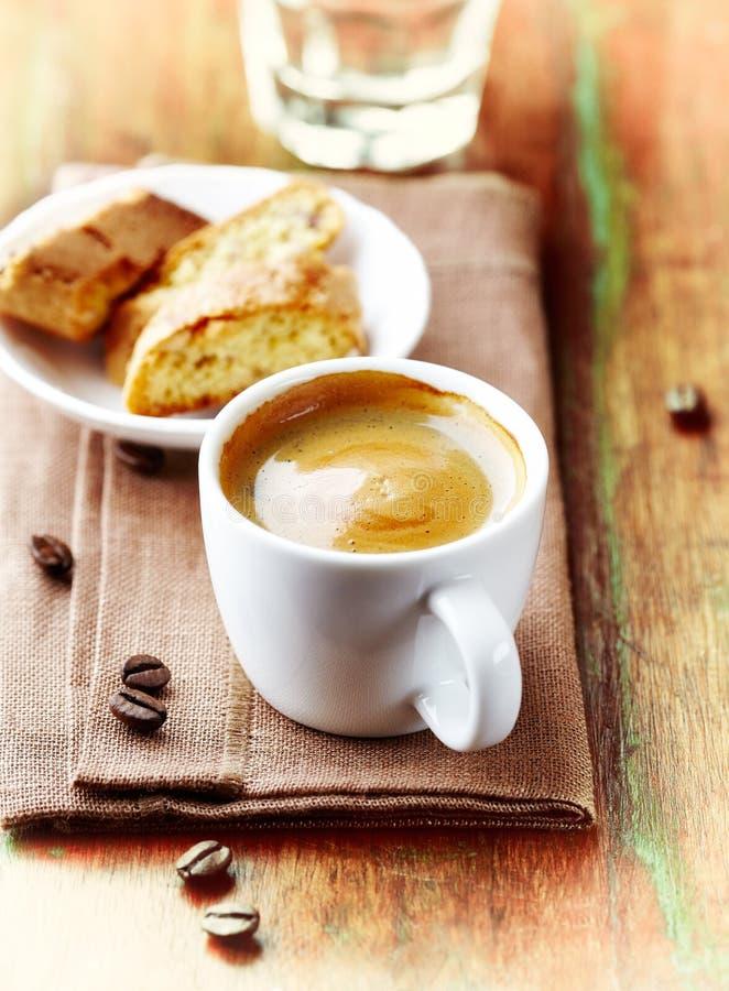 Kopp kaffe med en Biscotti Symbolisk bild lantligt trä för bakgrund royaltyfria bilder