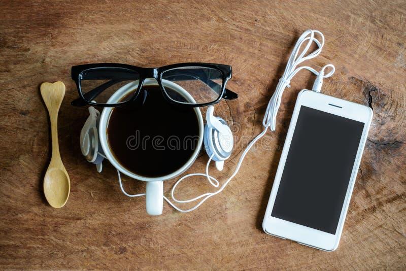 Kopp kaffe med hörluren och mobiltelefonen royaltyfri foto