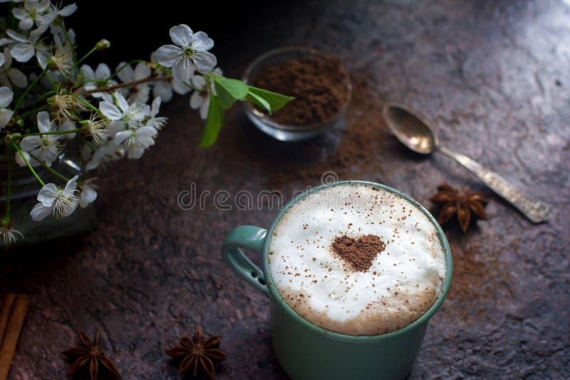 Kopp kaffe med hjärta av kakao-, kanel- och vårblommor på mörk stenbakgrund arkivfoton